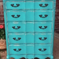 Large French chest of drawers in turquoise with black glaze accenting detailed areas. Distressing reveals previous white paint and wood tones. Original dark bronze pulls. From Facelift Furniture's Chests of Drawers collection.