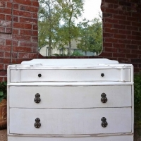 Vintage vanity and mirror in distressed Antiqued White with Tobacco glaze accenting wood grain. Three wide drawers with original pulls. From Facelift Furniture's Desk & Vanities collection.