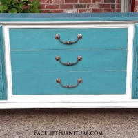 Mid-century modern buffet in distressed sea blue and off white, with black glaze. Doubles shelves behind side doors that swing open. Original pulls on drawers. A great option for a flat screen console.