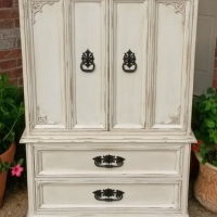 Clothing Armoire in distressed Off White with Tobacco Glaze. Two drawers and three storage compartments behind doors. Original pulls painted dark bronze. From Facelift Furniture's Chests of Drawers collection.