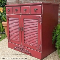 Maple Cabinet with louvered doors in Barn Red with Black Glaze. Ornate wood applique added on bottom, with distressing revealing white primer and original wood tones on entire piece. Two drawers. New ornate pulls. From Facelift Furniture's Red Refinished Furniture collection.