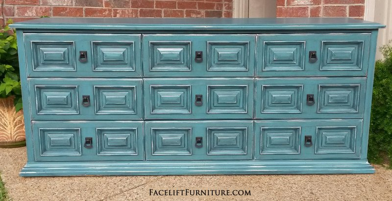 dresser in sea blue with black glaze nine drawers with distressing revealing white primer