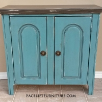 Cabinet in Sea Blue with Dark Brown top. Black Glaze, with distressing revealing white primer. Inside double shelf area in Sea Blue. Antique pulls. From Facelift Furniture's Sea Blue Furniture collection.
