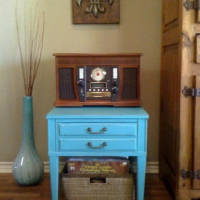 Stefanie purchased this antique end table, painted Turquoise, lightly distrssed and with Tea-Stained glaze. She used it for her record player, and the basket beneath holds her albums.