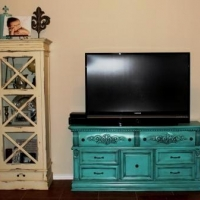 Eric & Maegan purchased this large ornate dresser for their flat screen. Dresser painted turquoise with heavy black glaze accenting detailed areas.