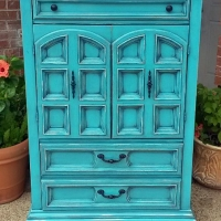 Clothing Armoire in distressed Turquoise with Black Glaze. Vintage pulls painted black. One drawer and 3 storage compartments behind the doors.