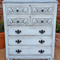 Art Deco Chest of Drawers in distressed Robin's Egg Blue. Black Glaze accents heavy wood grain and ornate detail. Five drawers, with pulls spray painted black. From Facelift Furniture's Chests of Drawers collection.