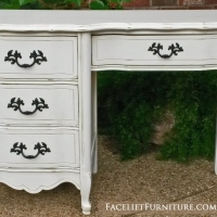 French desk in distressed antiqued white with light tea stained glaze. Original pulls painted dark bronze. From Facelift Furniture's Desk & Vanities collection.