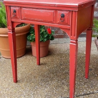 Vintage sewing cabinet in distressed Blazing Orange with Black Glaze. Repurposed as an end table. From Facelift Furniture's End Tables collection.