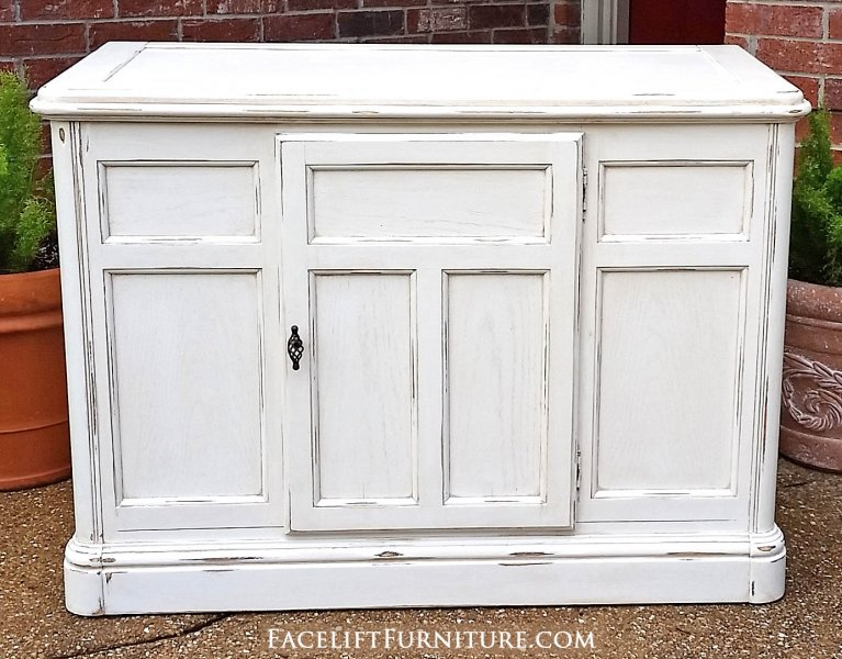 Cabinet in distressed off white with tobacco glaze. Middle door opens to double shelf area. From Facelift Furniture's Hutches, Cabinets & Buffets collection.
