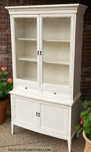 "China Cabinet in distressed Off White with Tobacco Glaze. Single wide drawer, and lower storage with shelf. Original pulls painted dark bronze. 72.5"" tall, 40"" wide, 17"" deep."