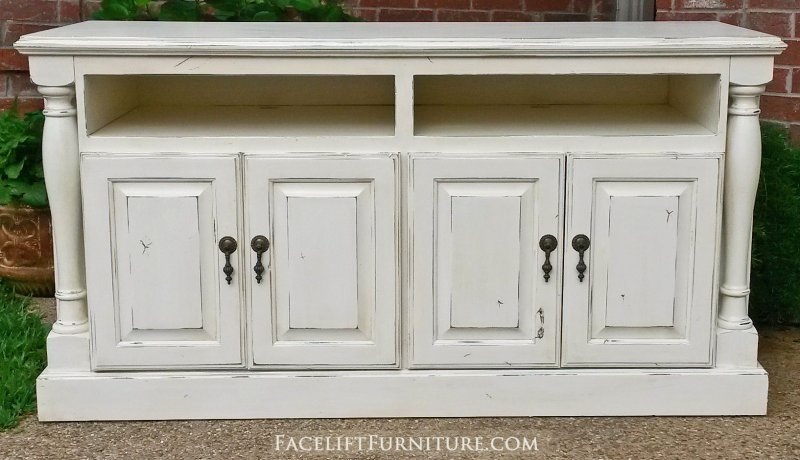 Large media console in distressed off white with tobacco glaze. Originally a custom built piece with knotty pine construction. Two upper compartments, with large storage spaces behind doors. Wiring holes go down to lower cabinets and out back of piece. Vintage pulls.