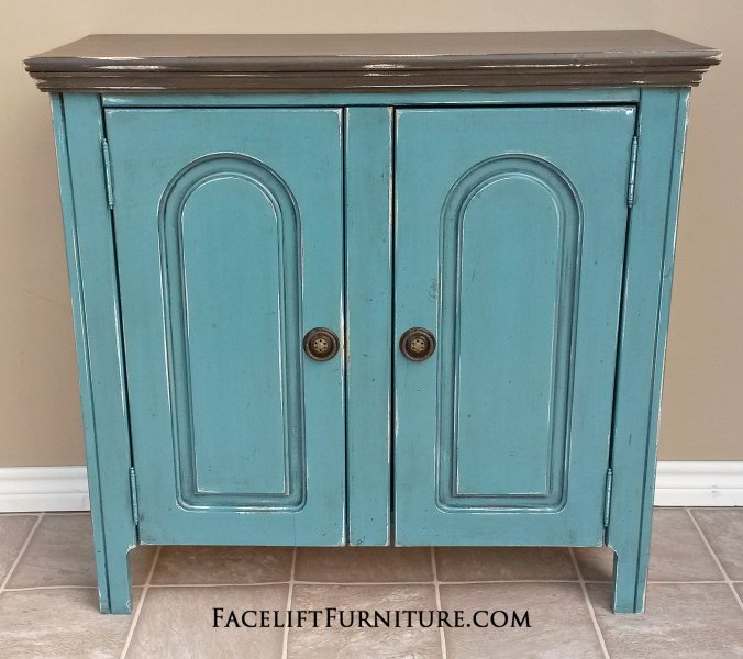 Cabinet in Sea Blue with Dark Brown top. Black Glaze, with distressing revealing white primer. Inside double shelf area in Sea Blue. Antique pulls. From Facelift Furniture's Hutches, Cabinets & Buffets collection.