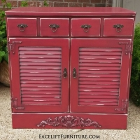 Maple Cabinet with louvered doors in Barn Red with Black Glaze. Ornate wood applique added on bottom, with distressing revealing white primer and original wood tones on entire piece. Two drawers. New ornate pulls.