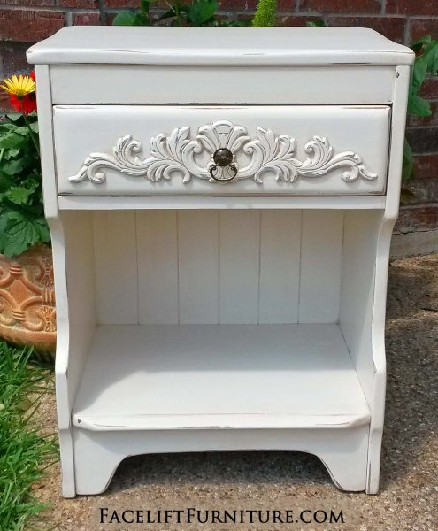 Ornate maple nightstand in distressed off white with tobacco glaze. Would repurpose great as a printer stand.