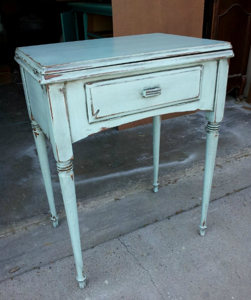 Antique sewing table in Robin's Egg Blue, with Black Glaze.  Distressing reveals while primer. From Facelift Furniture's Robin's Egg Blue Furniture collection.