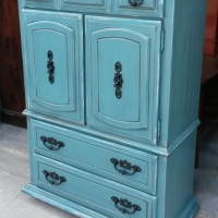 Armoire Chest in distressed Sea Blue with Black Glaze. Original pulls painted black.  Three drawers inside doors. From Facelift Furniture's Sea Blue Furniture collection.