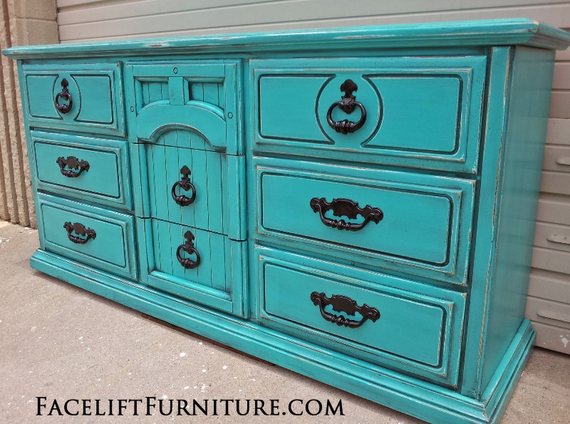 Large Dresser in Turquoise with Black Glaze distressed down to white primer. Top middle drawer pull built into the wood molding. All original hardware painted black. From Facelift Furniture's DIY Inspiration album.