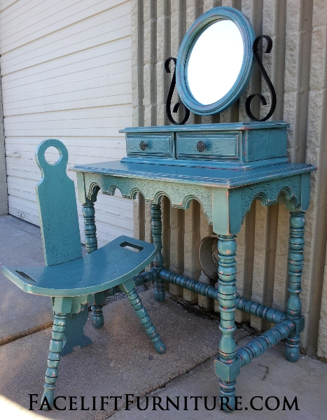 Vintage Vanity with Chair & Mirror, in Sea Blue with Black glaze accenting many detailed areas. Original color of piece was a red-orange, which peaks through in distressing. From Facelift Furniture's DIY Inspiration album.